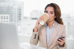 Attractive businesswoman drinking from disposable cup Stock Image