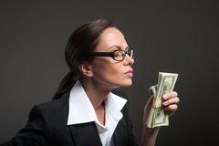 Attractive businesswoman enjoys smell of money on black background. Royalty Free Stock Image