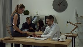 Two business colleagues discussing graph in office. Attractive businesswoman in eyeglasses with digital tablet discussing with her male colleague graphs at stock footage