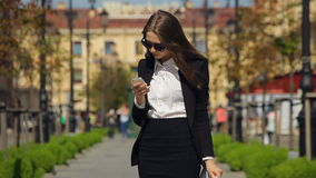 Attractive businesswoman in formal dress with clipboard on the street. stock footage