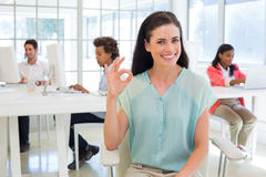 Attractive businesswoman giving OK sign to camera Royalty Free Stock Photos
