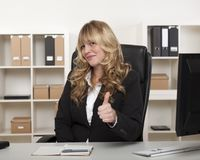 Attractive businesswoman giving a thumbs up Stock Photography