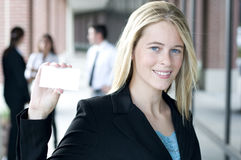 Attractive businesswoman holding a card. Attractive businesswoman holding out a blank card Royalty Free Stock Images