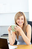 Attractive businesswoman holding cup using laptop Royalty Free Stock Photos
