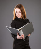 Attractive businesswoman holding a file with documents. Grey background Stock Images