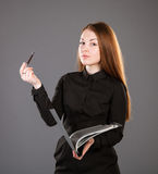 Attractive businesswoman holding a file with documents. Grey background Stock Photo