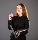 Attractive businesswoman holding a file with documents. Grey background Royalty Free Stock Photos