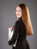 Attractive businesswoman holding a file with documents. Grey background Royalty Free Stock Photography