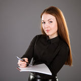 Attractive businesswoman holding a file with documents. Grey background Stock Image
