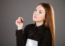 Attractive businesswoman holding a file with documents. And a pen, grey background Royalty Free Stock Photography