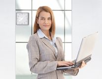 Attractive businesswoman holding laptop smiling Stock Photo