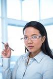 Attractive businesswoman holding pen Stock Photos