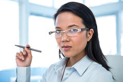Attractive businesswoman holding pen Stock Images