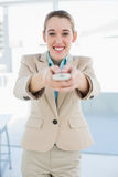 Attractive businesswoman holding a remote smiling cheerfully at camera Royalty Free Stock Images