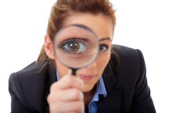 Attractive businesswoman holds magnifying glass. Search or spy concept, isolated on white Stock Photos