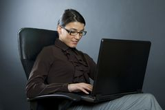 Attractive businesswoman with laptop seated Royalty Free Stock Images