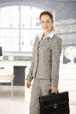 Attractive businesswoman leaving bright office Royalty Free Stock Image
