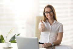 Attractive businesswoman looking at camera, showing thumbs up at. Workplace, pretty happy manager raising finger sitting at office desk with laptop, likes her Stock Photography