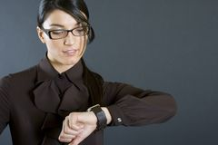 Attractive businesswoman looking at the watch royalty free stock images