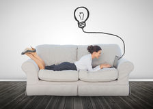 Attractive businesswoman lying on a couch and typing on her lapt Stock Images