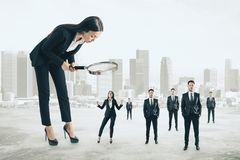 Supervision and manager concept. Attractive businesswoman with magnifier looking at businesspeople on blurry city background. Supervision and manager concept stock image