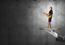 Attractive businesswoman on metal tray playing acoustic guitar against concrete wall background Royalty Free Stock Images
