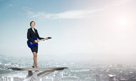 Attractive businesswoman on metal tray playing electric guitar against cityscape background Royalty Free Stock Photography