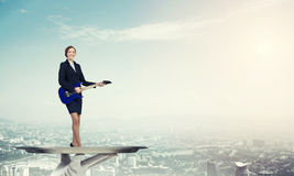 Attractive businesswoman on metal tray playing electric guitar against cityscape background Royalty Free Stock Photo