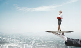 Attractive businesswoman on metal tray with red book in hands against cityscape background Stock Photography