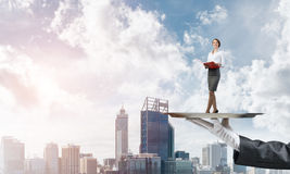 Attractive businesswoman on metal tray with red book in hands against cityscape background Stock Photos