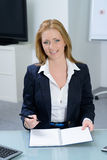 Attractive businesswoman in office smiles Royalty Free Stock Photography