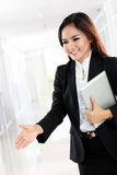 Attractive businesswoman with an open hand ready for handshake Royalty Free Stock Image