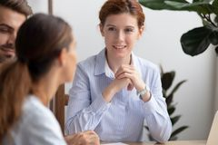 Attractive businesswoman owner hr manager listening vacancy candidates. Attractive businesswoman owner hr manager sitting at desk listening vacancy candidates royalty free stock images
