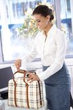 Attractive businesswoman packing bag in office Stock Image