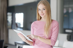 Attractive businesswoman portrait. Portrait of beautiful businesswoman using digital tablet while standing at office and working online Stock Photos