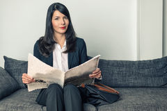 Attractive businesswoman reading a newspaper Stock Images