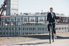 Attractive businesswoman riding bicycle on bridge. And holding shoes stock photography