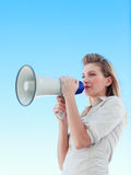 Attractive businesswoman shouting in a megaphone Stock Photo