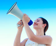 Attractive businesswoman shouting in a megaphone Stock Image