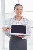Attractive businesswoman showing laptop screen and pointing at it Royalty Free Stock Photography
