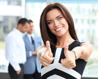 Attractive businesswoman showing thumbs up. Business concept - attractive businesswoman with team in office showing thumbs up Stock Images
