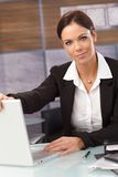 Attractive businesswoman shutting down laptop. Attractive young businesswoman shutting down laptop, looking at camera, sitting at desk royalty free stock photography