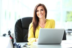 Attractive businesswoman sitting on a desk with laptop in the office. Royalty Free Stock Images