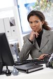 Attractive businesswoman sitting at desk in office Stock Photography
