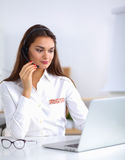 Attractive businesswoman sitting  on desk in the Royalty Free Stock Images