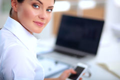 Attractive businesswoman sitting on desk in the office. Attractive businesswoman sitting in the office Stock Images