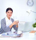 Attractive businesswoman sitting  on desk in the Stock Photography