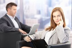 Attractive businesswoman sitting in office lobby Stock Photo