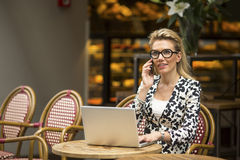 Attractive businesswoman sitting outdoors with laptop and talking on a cell phone. Stock Photo
