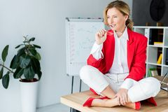 Attractive businesswoman sitting on table and biting glasses. In office royalty free stock photos